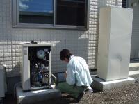 ガスエンジン発電ユニットの前側をはずして取り替えています。